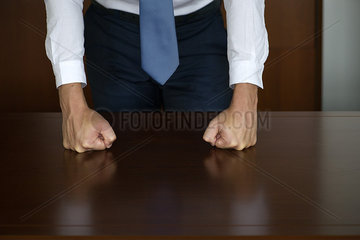 Businessman pounding fists on table  cropped