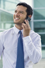 Businessman using cell phone  smiling