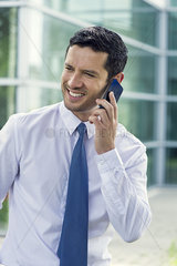 Businessman talking on cell phone and smiling outdoors