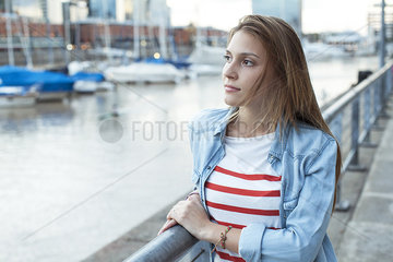 Young woman leaning against railing  looking at view