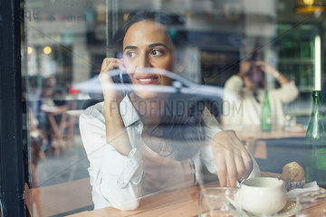 Woman talking on cell phone in coffee shop