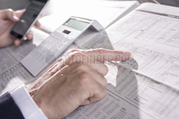 Checking stock market performance in newspaper
