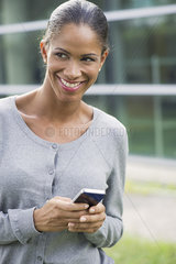 Woman using smartphone and smiling outdoors