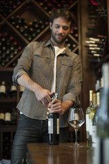 Sommelier uncorking bottle of wine