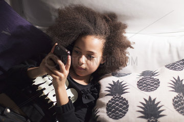 Girl lying down  using smartphone