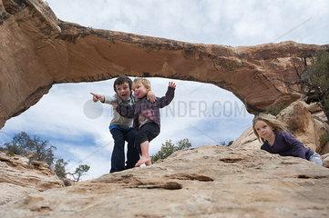 Children exploring near Owachomo Bridge  Natural Bridges National Monument  Utah  USA