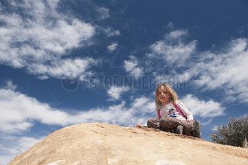 Little girl sitting on top of rock  portrait