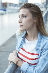 Young woman leaning against railing  looking at view of water