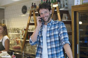 Shopkeeper taking phone call
