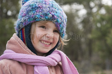 Little girl wearing knit hat and scarf  smiling  portrait