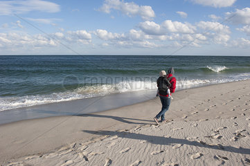 Vacationer walking on beach with small child on back during the off season