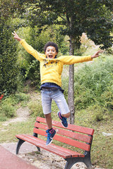Boy jumping off bench