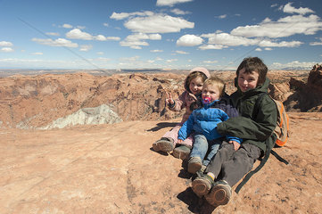 Children sitting at edge of canyon in Canyonlands National Park  Utah  USA