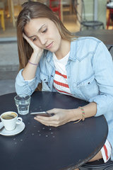 Young woman text messaging in cafe