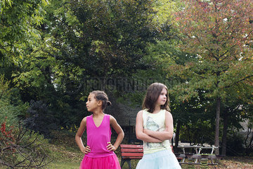 Girls standing together outdoors  both looking away angrily