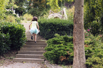 Girl in tutu running up stairs in park  rear view