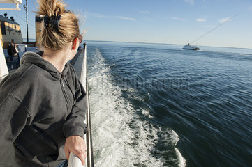Woman standing on deck of ferry boat  looking over shoulder at view