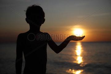 Kaegsdorf  Deutschland  Silhouette  ein Kind haelt eine Hand unter die untergehende Sonne