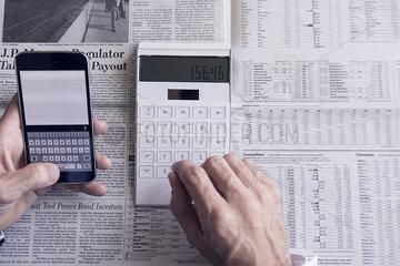 Investor using smartphone and calculator