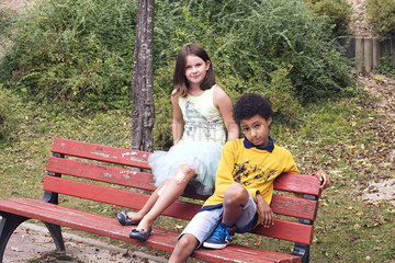 Children sitting together on park bench