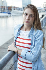 Young woman leaning against railing  portrait