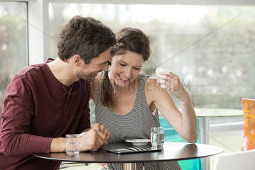 Couple in cafe watching video streaming on digital tablet