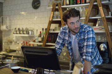 Cafe owner standing behind cash register