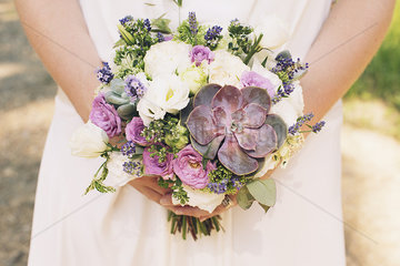Bride holding bouquet of flowers and succulent plants  cropped