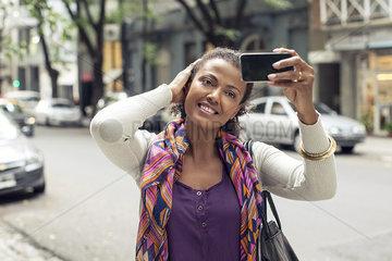 Woman taking selfie on street