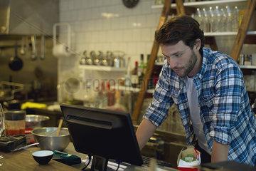 Cafe owner looking at cash register