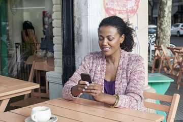 Woman using cell phone at sidewalk cafe
