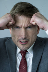 Businessman holding clenched fists against head in anger  portrait
