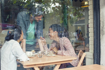 Waiter talking to customers in coffee shop