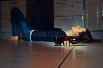 junge Frau liegt mit einer Bierflasche auf dem Fussboden der Kueche