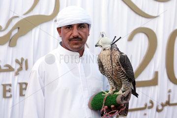 Dubai  Vereinigte Arabische Emirate  Araber haelt einen Sakerfalken mit Haube auf der Hand
