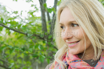 Mature woman looking away and smiling outdoors  portrait