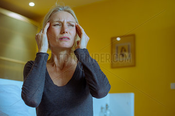 Mature woman massaging temples while suffering a headache