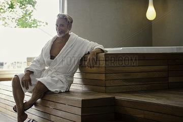 Man in bathrobe relaxing in sauna room