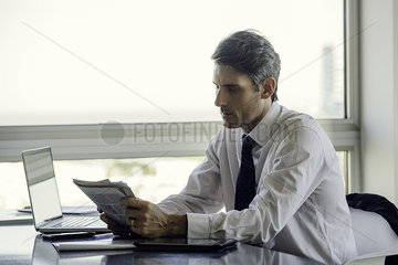 Man reading newspaper in office