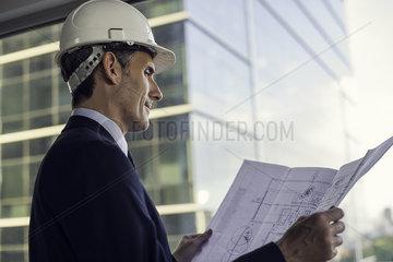 Man wearing hard hat reviewing blueprint