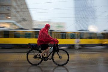Berlin  Deutschland  Radfahrer im Regen auf dem Alexanderplatz