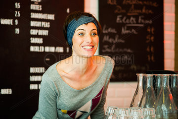 Woman smiling cheerfully in restaurant  portrait