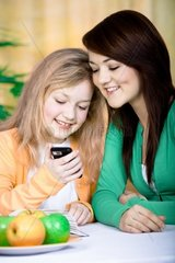 two girls with a cellphone at home