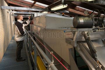 Guebwiller  Frankreich  Arbeiter an der modernen Weinpresse in der Weinkelterei Domaines Schlumberger