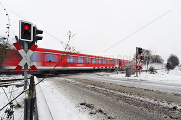 Personenzug passiert einen Bahnuebergang