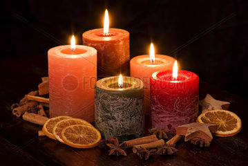 Colored Candlelight with decoration as closeup on a wood table
