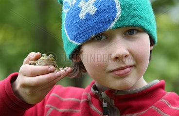 Neu Kaetwin  Deutschland  Junge haelt einen Teichfrosch in der Hand