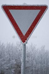 Vereistes und verschneites Vorfahrt Achten Verkehrsschild