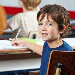 Laechelndes Kind sitzt am Tisch in Schule