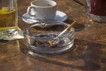 Brennende Zigarette in einem Aschenbecher auf einem Wirtshaustisch